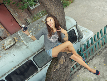 teenage girl happy: Urban girl has fun with vintage photo cameras outdoor near tree and retro car, image toned.