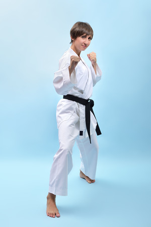 girl action: fighting karate girl, young woman with black belts - champions of the world, over blue background studio shot  Stock Photo