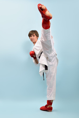 girl kick: fighting karate girl, young woman with black belts - champions of the world, over blue background studio shot  Stock Photo
