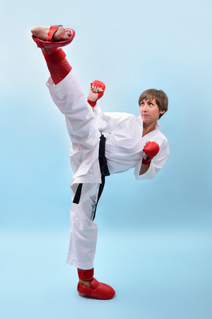 fighting karate girl, young woman with black belts - champions of the world, over blue background studio shot  photo