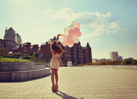 windy city: Happy young woman is whirling in park over city background and holding air balloons, toned.