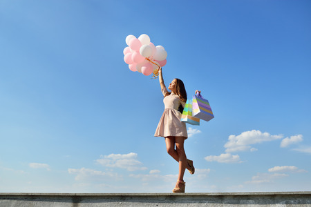Gyönyörű lány gazdaság bevásárló táskák és színes lufik fölött kék ég Stock fotó