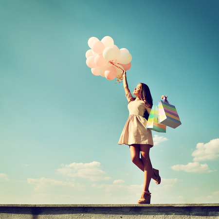Beautiful girl holding shopping bags and colored ballons over blue sky, toned photo