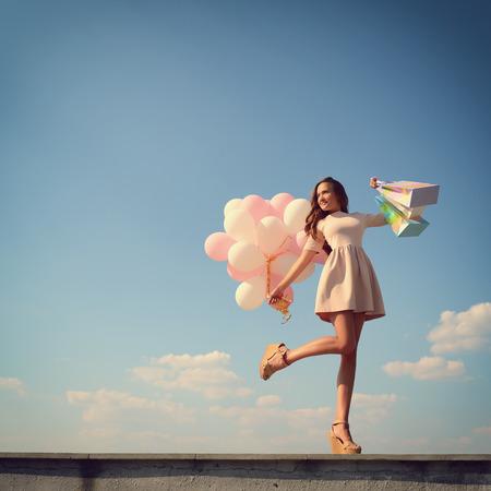 Bella ragazza che tiene borse della spesa e palloncini colorati nel cielo blu, tonica.
