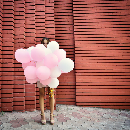 weather balloon: happy young woman standing over red brick wall and holding pink and white balloons