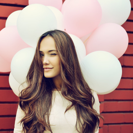 赤レンガの壁と持株ピンクとホワイトで幸せな若い女風船し、ウィンクを与えます。イメージのトーン。