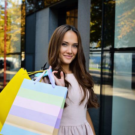 Mooie jonge mode vrouw met boodschappentassen en staan in de buurt etalage, afgezwakt Stockfoto