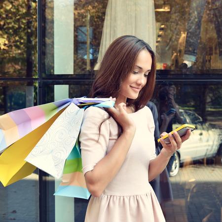 ショップ ウィンドウの呼び出し元のスマート フォン、近くにショッピング袋を持つ美しい若いファッション女性トーン
