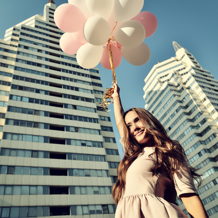 Beautiful young girl holding colored ballons over high-rise building. Urban teenage background. Toned. photo