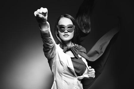 Piuttosto giovane donna che apre la sua camicia come un supereroe. Super ragazza, immagine tonica. Beauty salva il mondo. Bianco e nero. Archivio Fotografico