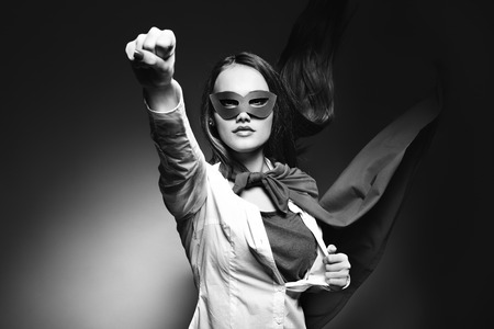 super human: Young pretty woman opening her shirt like a superhero. Super girl, image toned. Beauty saves the world. Black and white.