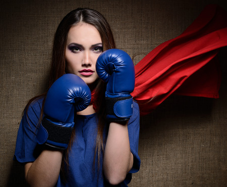 female boxing: Young pretty woman opening her t-shirt like a superhero. Super girl, image toned. Beauty saves the world.