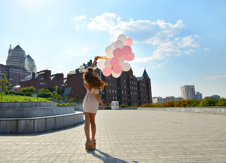 windy city: Happy young woman is whirling in park over city background and holding air balloons Stock Photo