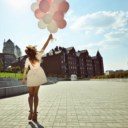 Boldog fiatal nő örvénylő parkban át városi háttér és a gazdaság hőlégballonok, tónusú. Stock fotó
