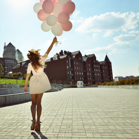 Happy young woman is whirling in park over city background and holding air balloons, toned.