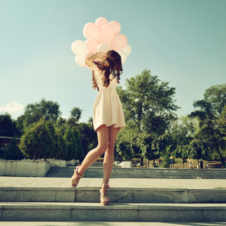 Fashion girl with air balloons steps on stairs, image toned.