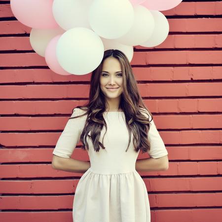 Boldog fiatal nő állt a piros téglafal és a gazdaság rózsaszín és fehér léggömb. Öröm. Álmok. Tónusú.