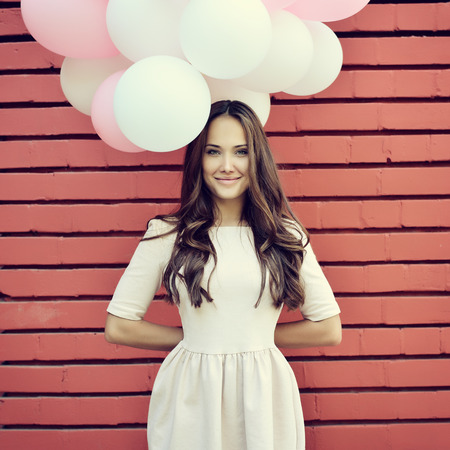 Happy young woman standing over red brick wall and holding pink and white balloons. Pleasure. Dreams. Toned.