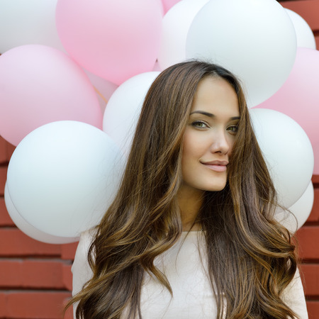 weather balloon: Happy young woman standing over red brick wall and holding pink and white balloons. Pleasure. Dreams.