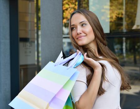 美しい若者のファッションの女性の買い物袋を保持していると、店の窓の近くに立って 写真素材
