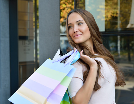 Beautiful young fashion woman holding shopping bags and standing near shop window 스톡 콘텐츠