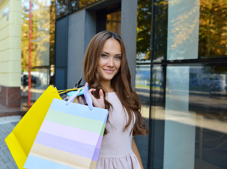Beautiful young fashion woman holding shopping bags and standing near shop window photo
