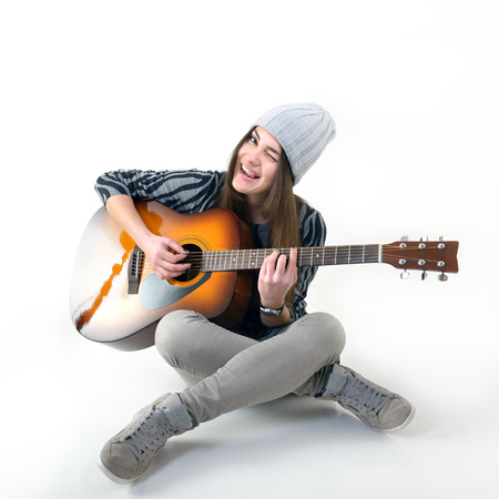 mladá žena hraje hudbu na akustickou kytaru