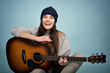 young woman playing music on acoustic guitar, toned Stockfoto
