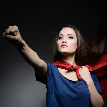 courageous: Superwoman. Young pretty woman opening her shirt like a superhero. Super girl, image toned. Beauty saves the world.
