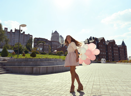whirling: Happy young woman is whirling in park over city background and holding air balloons, toned.