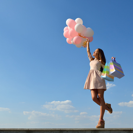 ballons: Beautiful girl holding shopping bags and colored ballons over blue sky