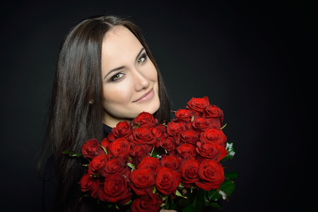 woman black background: Beautiful Woman with Fresh Red Roses. Girl and Flowers over Black Background. Beauty Female Face. Happiness, Freshness, Beauty, Youth. Stock Photo