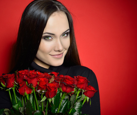 sexy birthday: Beautiful Woman with Fresh Red Roses. Girl and Flowers over Red Background. Beauty Female Face. Happiness, Freshness, Beauty, Youth. Stock Photo
