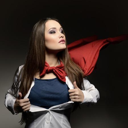 スーパーウーマン。スーパー ヒーローのように彼女のシャツを開いて若いきれいな女性。スーパー ガールは、トーンのイメージ。美は世界を救いま