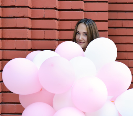 hapiness: Happy young woman standing over red brick wall and holding pink and white balloons. Pleasure. Dreams.