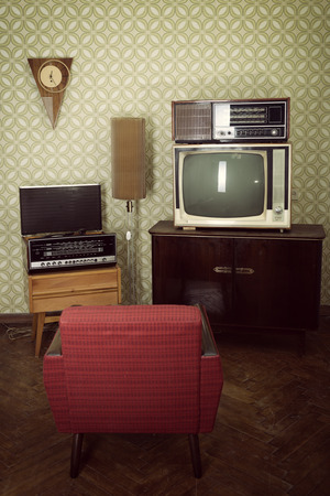 Vintage room with wallpaper, tv, old fashioned armchair, retro player, loudspeakers, clocks and standart lamp, toned Stock Photo