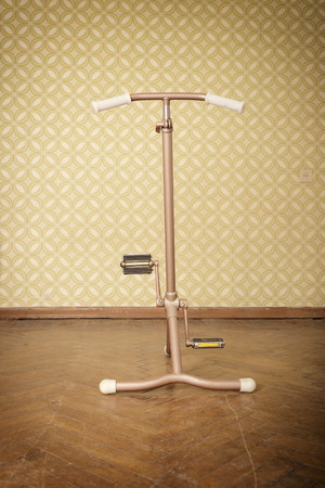 stationary bicycle: vintage stationary bicycle is in retro room. velosimulator