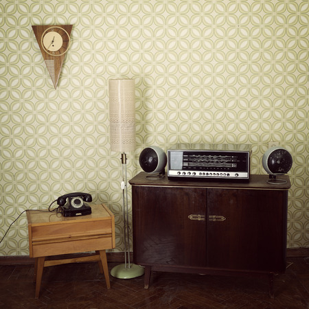 old fashioned: Vintage room with wallpaper, telephone, old fashioned furniture, retro player, loudspeakers, clocks and standart lamp, toned