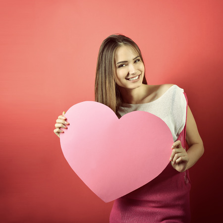 ragazza innamorata: Love and valentines day woman holding heart and smiling over pink background Archivio Fotografico