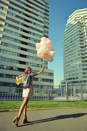 elegant girl: Beautiful young girl holding colored balloons over high-rise building