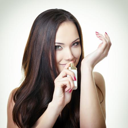 giovane donna bella azienda bottiglia di profumo e odorare profumo