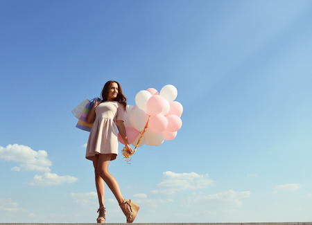 beautiful sky: Beautiful girl holding shopping bags and colored balloons over blue sky Stock Photo