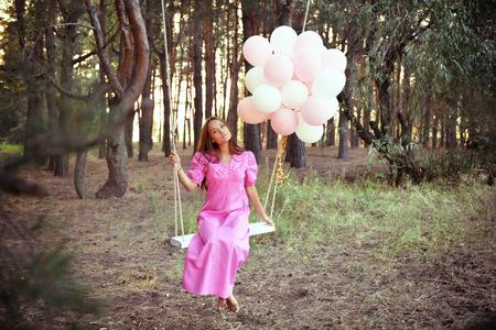 anochecer: Mujer joven en vestido retro de color rosa se balancea en un columpio en el bosque de pinos de verano