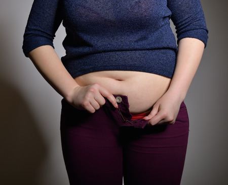 tight fitting: Obese woman trying to close the buttons of her jeans