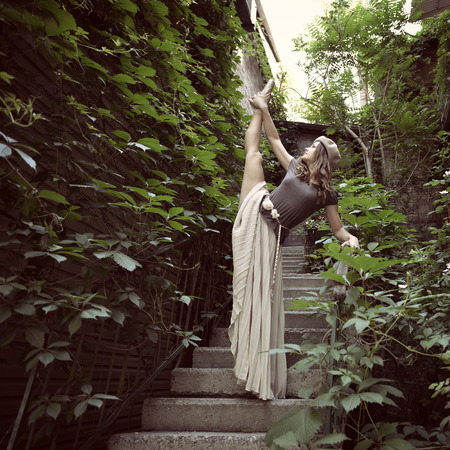svelte: Romantic image of young beautiful girl ballet dancer posing on stairs near old house, vintage toned