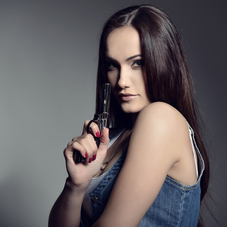 army girl: Beautiful girl with gun, studio shot.