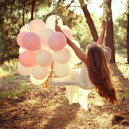 若い女性は夏松の森のブランコに揺れてください。 写真素材