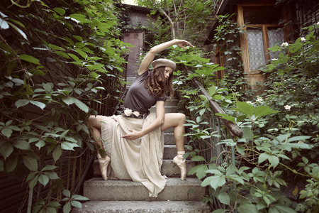style woman: Romantic image of young beautiful girl ballet dancer posing on stairs near old house, vintage toned