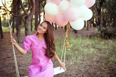 vestido de noche: Mujer joven en vestido retro de color rosa se balancea en un columpio en el bosque de pinos de verano