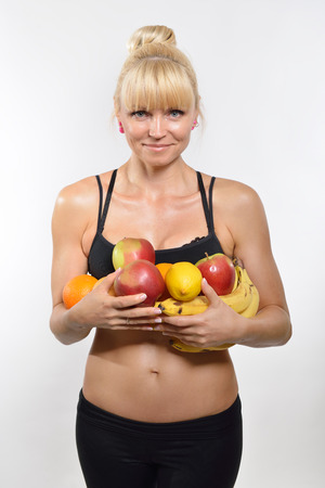 muscular body: Attractive happy middle-age fit woman holding fruit and vegetables